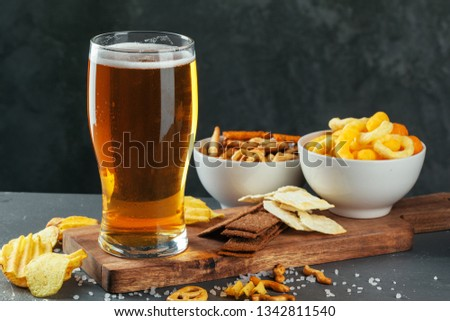 Glass of lager beer with snack bowls on dark stone background #1342811540