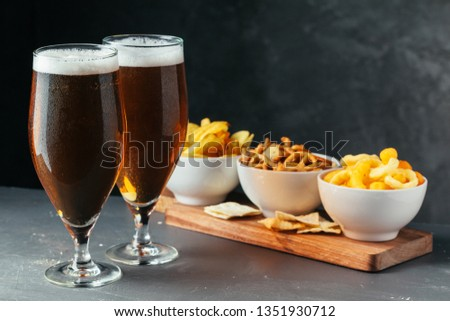 Glass of lager beer with snack bowls on dark stone background #1351930712