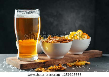 Glass of lager beer with snack bowls on dark stone background #1359323333