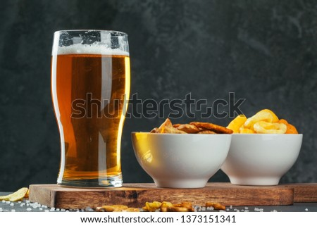 Glass of lager beer with snack bowls on dark stone background #1373151341