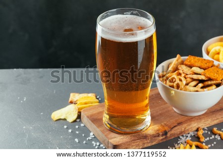 Glass of lager beer with snack bowls on dark stone background #1377119552