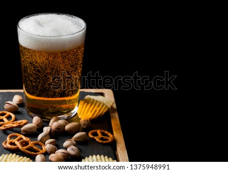 Glass of lager beer with snack on stone board on black background. Pistachios and pretzel with potato crisps #1375948991