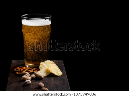 Glass of lager beer with snack on stone board on black background. Pistachios and pretzel with potato crisps #1375949006