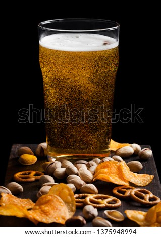 Glass of lager beer with snack on vintage wooden board on black. Pistachios and pretzel with potato crisps #1375948994
