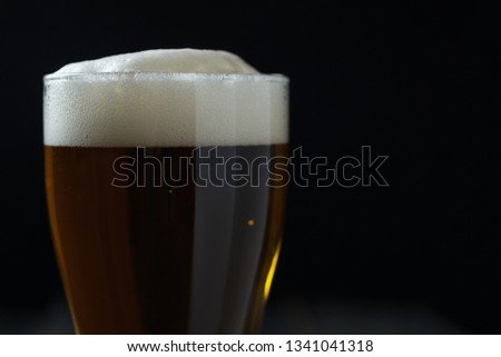 Glass of lager on a dark background #1341041318