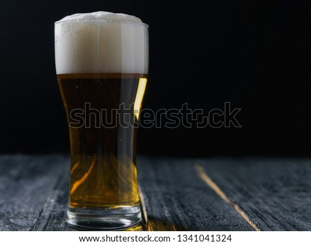 Glass of lager on a dark background #1341041324