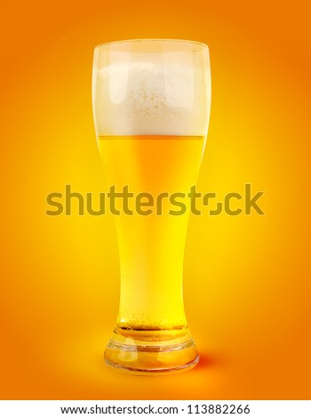 glass of light beer on orange yellow abstract background