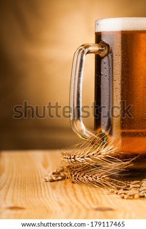 Glass of light beer on table