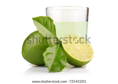 Glass of lime juice and lime fruits with green leaves isolated on white