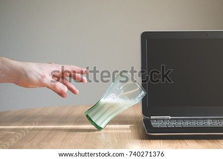 Glass of liquid is about to fall and spill on the keyboard of a laptop. Person trying to reach for the glass. Insurance or warranty concept. Bad luck concept. Stockfoto ©