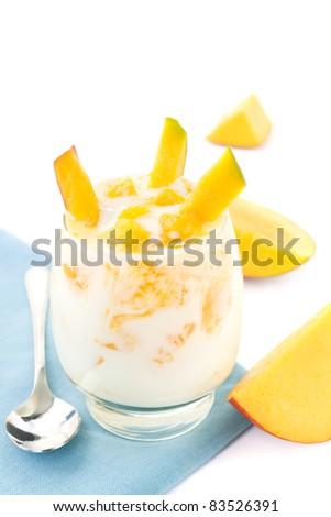 Glass of mango yogurt with spoon and mango pieces