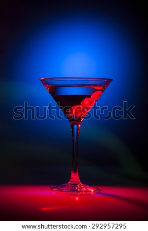 Glass of martini cocktail with red cherries on a mixed color background.