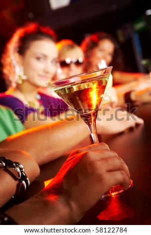 Glass of martini on background of row of smart teens in the nightclub