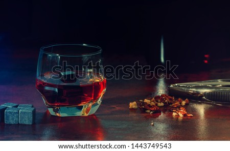 Glass of matured malt whisky with chilling cube and chopped nuts on a rustic wooden counter at night with bottle opener in a low angle view