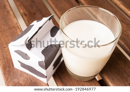 glass of milk, a carton of milk on wooden table.