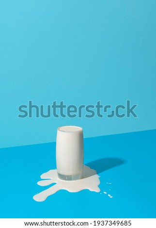 Glass of milk overflowing on a blue background in bright light. Spilled milk puddle and glass of milk on a colored table. Foto stock ©