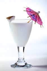 Glass of milk with a slice of coconut and a cocktail umbrella isolated on a white background