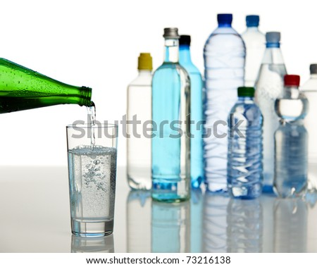 glass of mineral water being filled, various bottles in background, selective focus