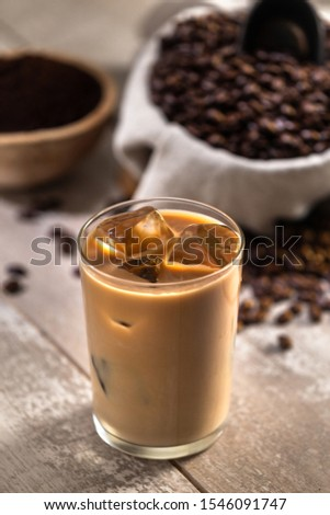 Glass of mocha latte ice coffee espresso with ingredients, whole roasted beans, scoop, grind, bag on wood  #1546091747
