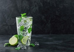 Glass of Mojito cocktail with ice cubes mint and lime on black board with fresh limes. Sparkling refreshing water. Space for text