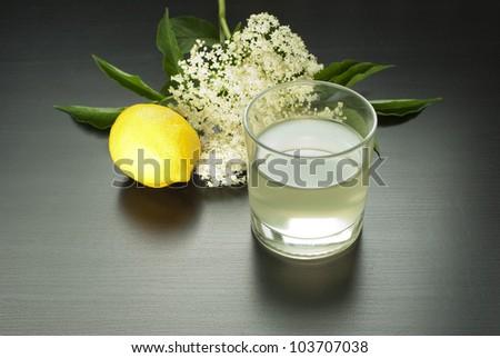 glass of natural elderflower juice with lemon and elder-flowers