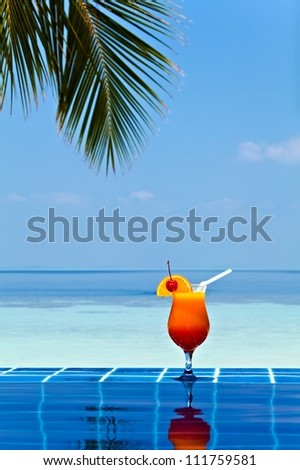 Glass of orage juice is on edge of pool made from glazed tile  in tropical hotel, Maldives
