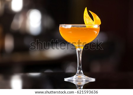 Glass of orange cocktail decorated with lemon at bar counter background. #621593636
