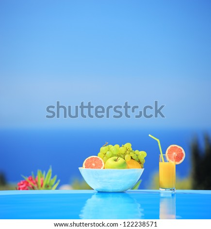 Glass of orange juice and bowl of various fruits next to a swimming pool, shot with a tilt and shift lens