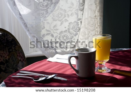 Glass of orange juice and cap of coffee on a table chair highlighted by the sunlight from  the window. - stock photo