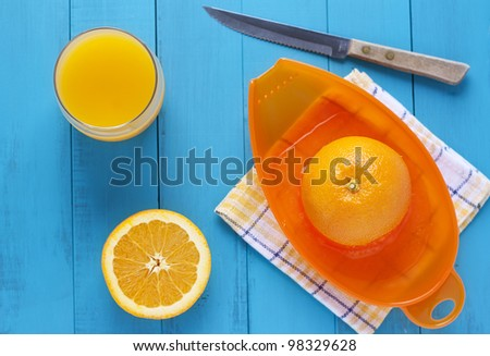 glass of orange juice and squeezed orange against blue table top