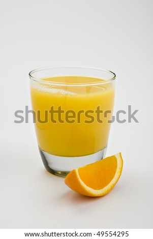 Glass of orange juice isolated on white with orange wedge in foreground