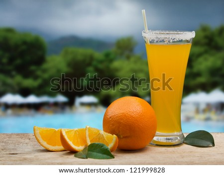 Glass of orange juice on a beach table