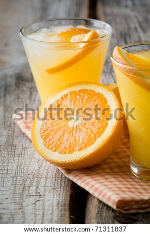 Glass of orange juice with ice cubes, selective focus