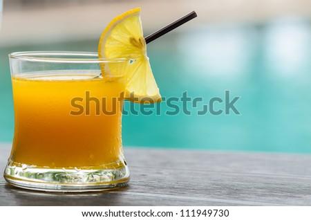 Glass of orange juice with orange slice with pool background