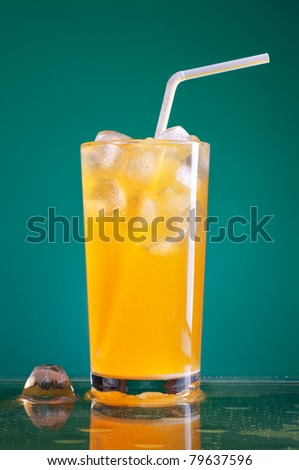 glass of orange soda with ice and straw over blue background