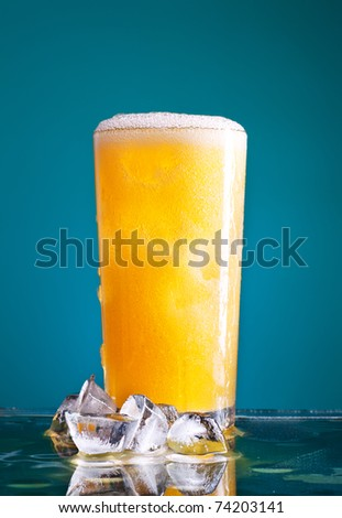 glass of orange soda with ice over blue background
