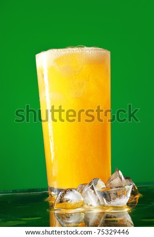 glass of orange soda with ice over green background