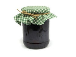 glass of plum jam on a white background