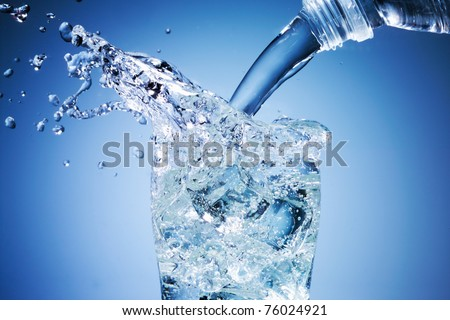 Glass of pouring water with ice