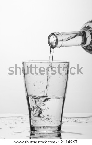 glass of pouring water with reflection (white background)