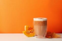 Glass of pumpkin latte, leaf and pumpkin on orange background