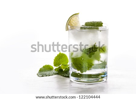 Glass of pure mineral water with leaves and ice