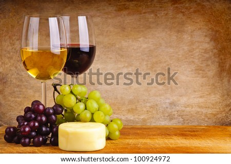glass of red and white wine, cheese and grapes on a wooden background
