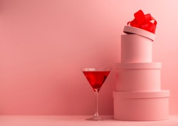 Glass of red cocktail and pink round gift boxes on background of the same color with copy space. Party, celebration concept.
