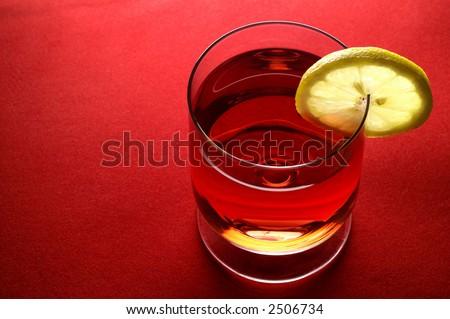 Glass of red liquid (wine,  tea, etc.) with lemon slice (horizontal) in red background