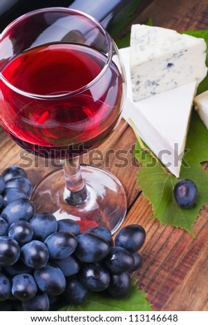 glass of red wine and grapes are ripe. Focus on a glass of wine.