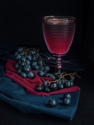 Glass of red wine and grapes on a black background . Stilllife with red wine and grapes .  Grapes for wine
