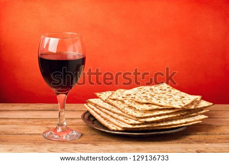 Glass of red wine and matzo on wooden table over grunge red background