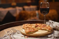 Glass of red wine and pieces of placida with cottage cheese or vertuta on a wooden tray, close-up, traditional Romanian, Moldavian or Balkan pie