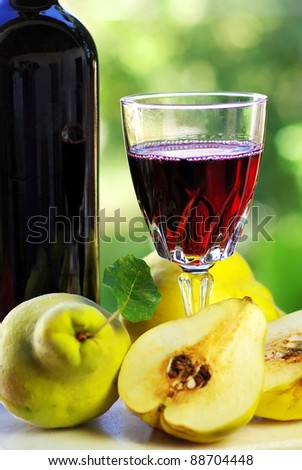 Glass of red wine and quince fruits.
